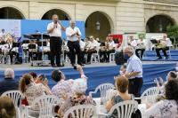 El concejal de Cultura y el director de la Banda, en el escenario, con el compositor de pie entre el público ,